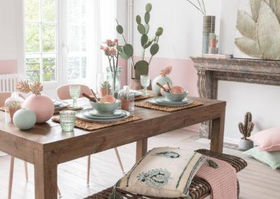Deko Artikel in weiß und rosa auf einem dunklen Holztisch