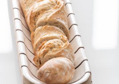 Aufgeschnittenes Baguette liegt in beiger Baguetteschale aus Holz