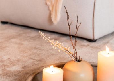 beige Vase und zwei weiße Kerzen