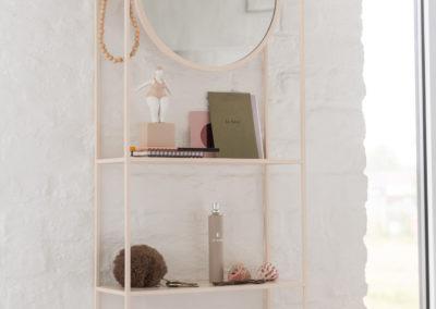 Schlichtes Regal aus rosa Lack mit rundem Spiegel