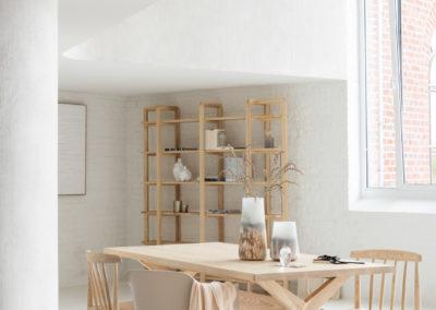 Esszimmer mit Schaukelstuhl und weiteren Holzstühlen schlicht beige-weiß eingerichtet