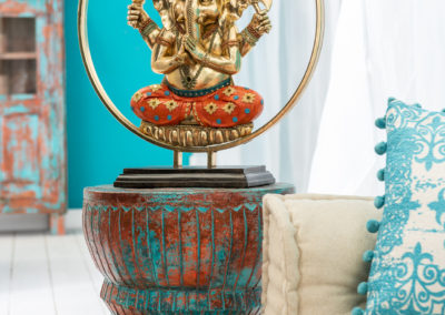 Großer goldener Elefant steht auf türkis orangenem Hocker