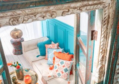 Kissen mit orientalischen Textilprint in orange und türkis liegen auf einer Couch