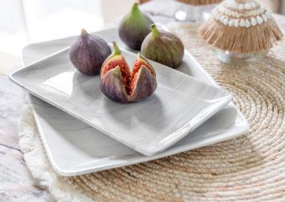 Tisch Untersetzer mit Quasten mit edlem Geschirr auf dem Früchte liegen