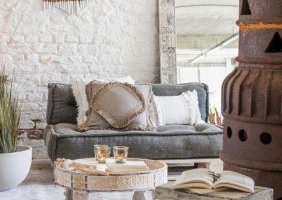 weiße Waschmöbel aus Holz stehen vor einem Longe-Sessel