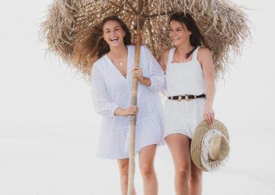 Zwei Frauen tragen Sonnenschirm aus Bast am Strand