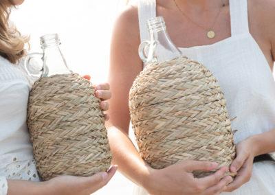 zwei Frauen tragen geflochtene Flaschen
