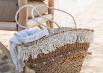 geflochtene Tasche mit Tuch und Magazin innenliegend lehnen an einer Holzbank
