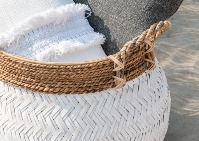 weißes und graues Kissen mit besonderem Muster liegen im Bastkorb