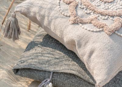 Zwei Kissen mit Quasten liegen am Strand