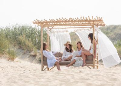 Große Bank mit leichten Schals auf der vier Frauen sitzen und entspannen