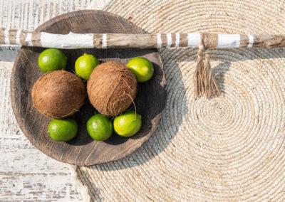 weisse Muster auf einem Stock und Schale mit Kokosnuss und Limetten