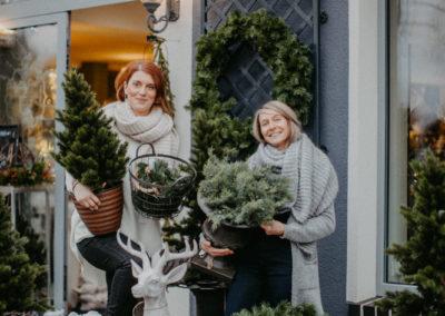 Zwei Frauen halten Weihnachtsbäume und weihnachtliche Deko in der Hand