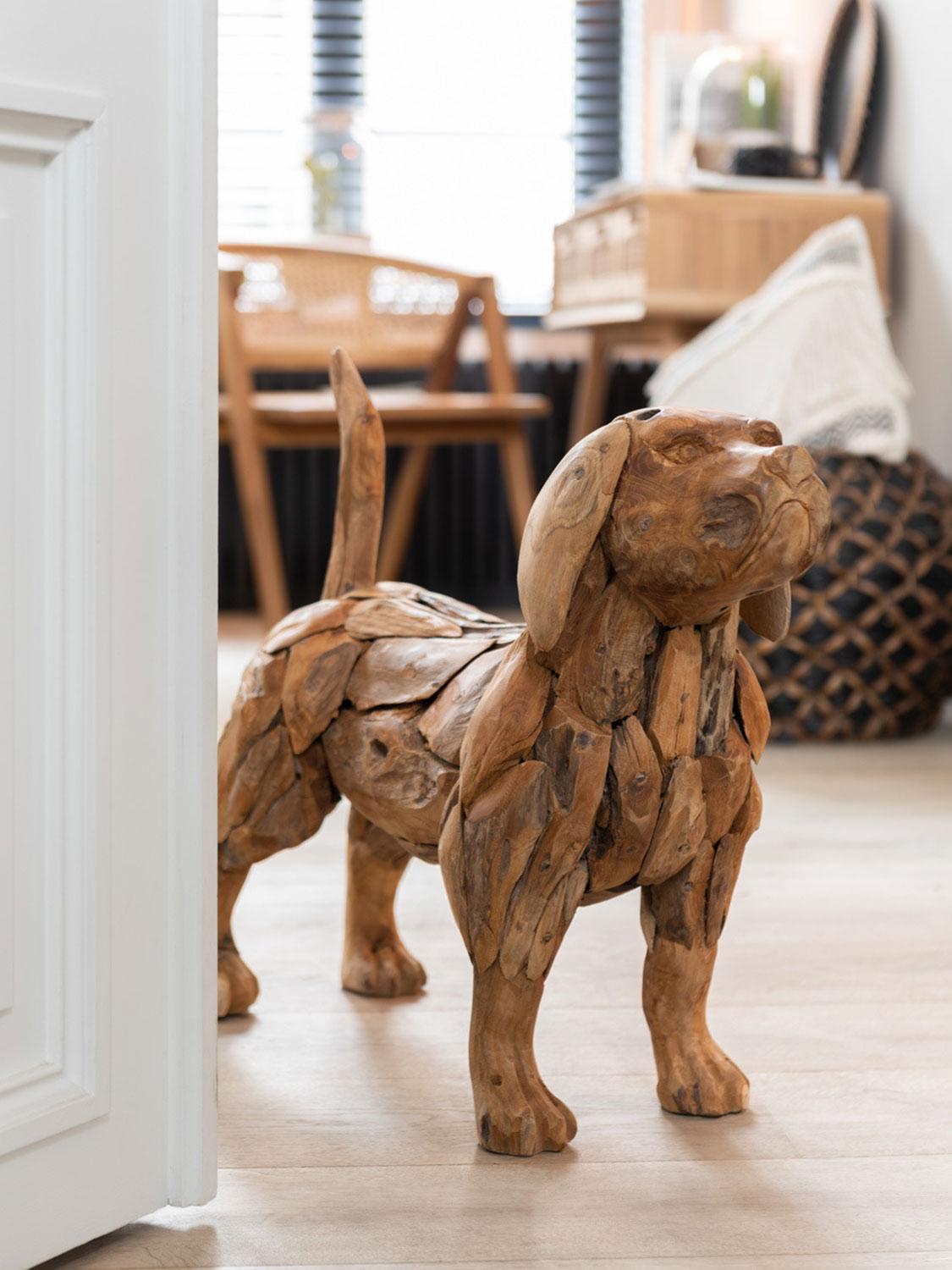 Hund als Holzfigur steht auf Boden