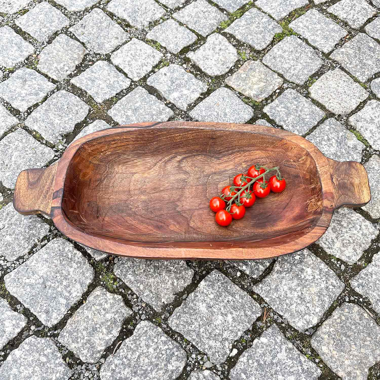 kleine Tomaten liegen in brauner Holzschale
