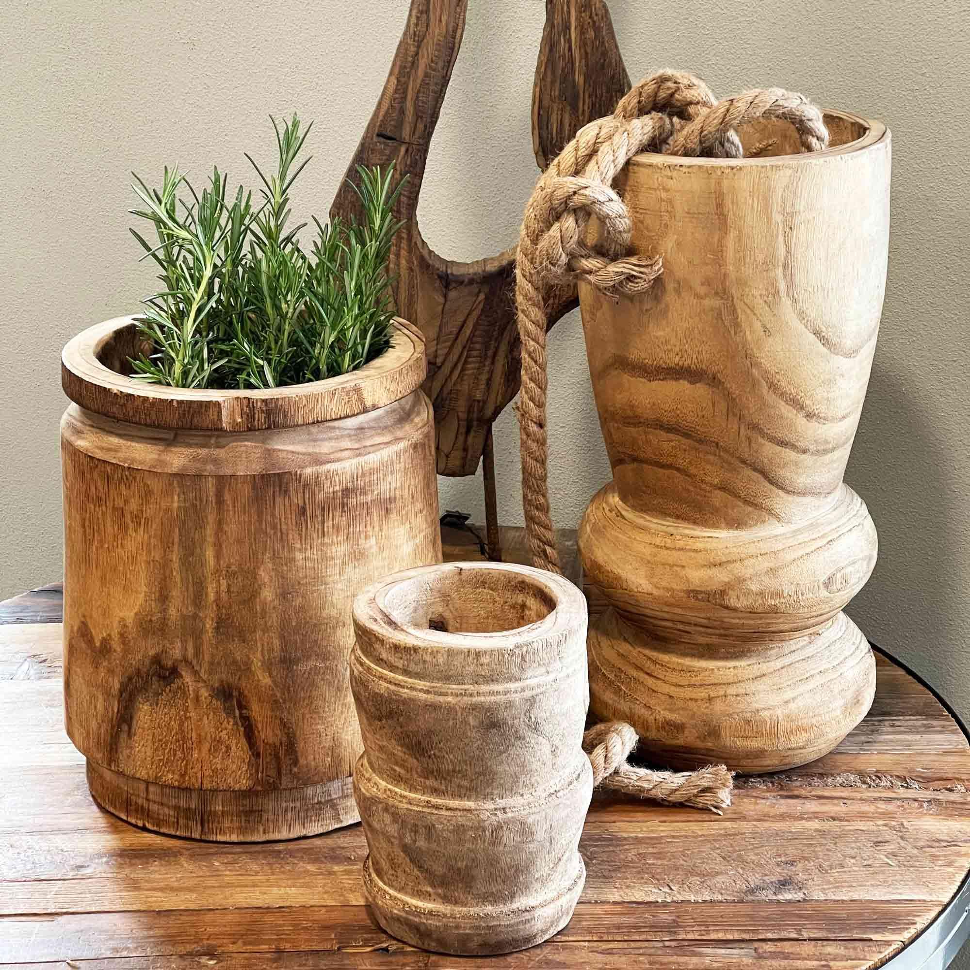 Vasen aus Holz vor grauer Wand